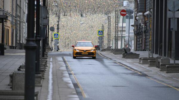 Такси едет по Столешникову переулку в Москве