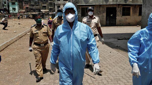 Медицинские работники в защитных костюмах в сопровождении сотрудников полиции в Мумбаи