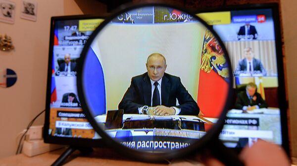 Трансляция совещания президента РФ Владимира Путина с главами регионов по борьбе с распространением коронавируса в России на экране телевизора