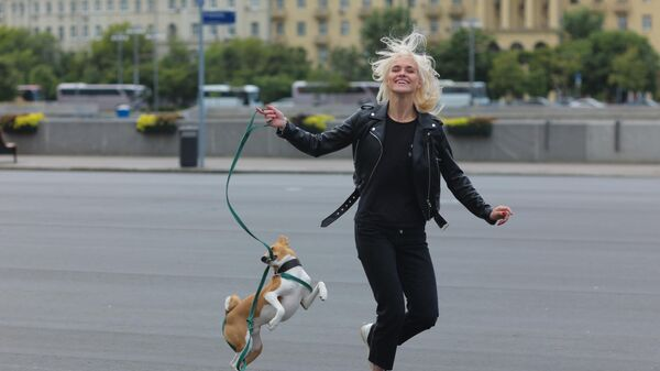 Девушка гуляет с собакой в Центральном парке культуры и отдыха имени Горького в Москве