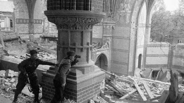 Советский офицер ведет корректировку артиллерийского огня на разрушенных улицах Берлина