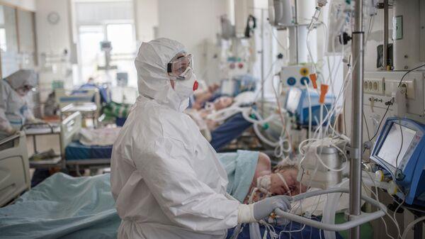 Пациент и медицинский работник в отделении реанимации и интенсивной терапии в стационаре для больных с коронавирусной инфекцией