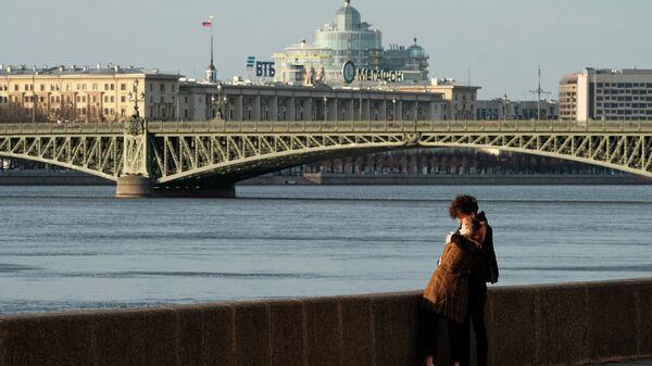 Молодые люди на Дворцовой набережной в Санкт-Петербурге