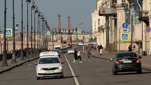 Люди переходят дорогу на Дворцовой набережной в Санкт-Петербурге