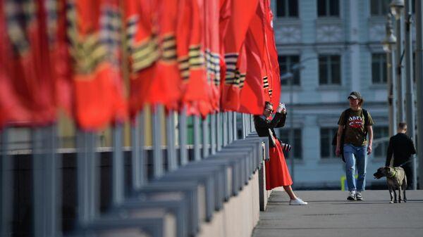 Девушка фотографируется у флагов, установленных к празднованию Дня Победы, на Москворецкой набережной в Москве