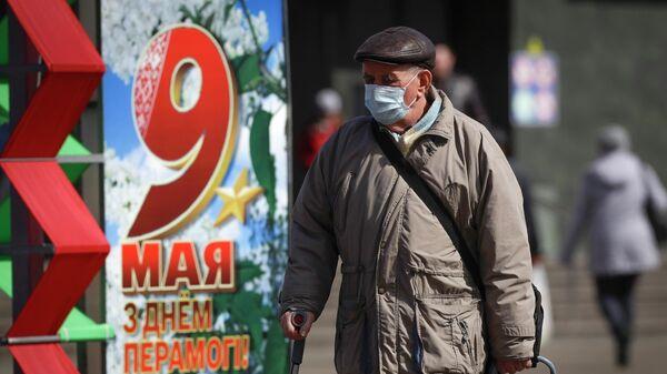 Мужчина проходит мимо украшений ко Дню Победы в Минске, Белоруссия