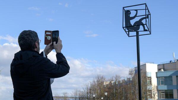 Мужчина фотографирует памятник самоизоляции в виде куба с силуэтами человека и кошки в Санкт-Петербурге