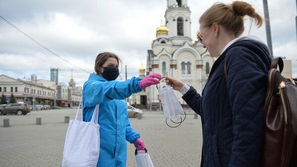 Волонтер раздает многоразовые маски на улице в Екатеринбурге