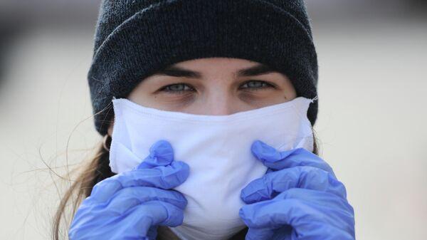 Девушка в маске и перчатках