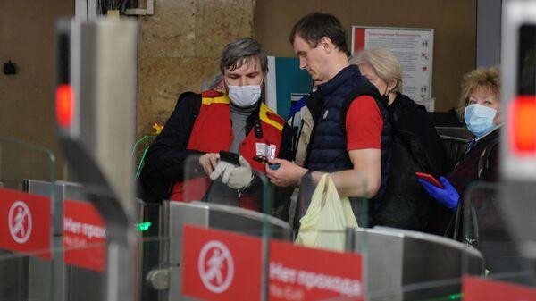 Сотрудник московского метро помогает пассажиру пройти через турникеты