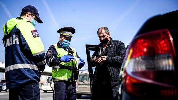 Сотрудники дорожно-патрульной службы ГИБДД во время проверки наличия пропуска у водителя на блокпосту на пересечении Варшавского шоссе с МКАД