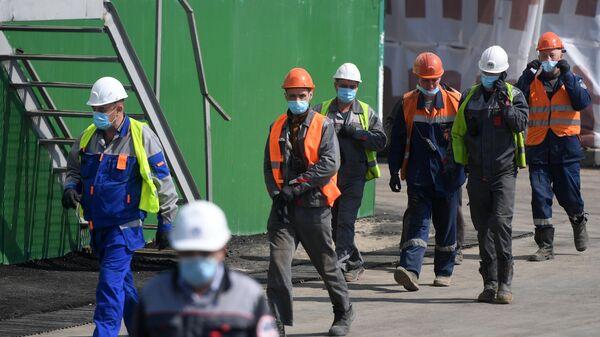 Рабочие в защитных масках во врем строительства станции метро Кленовый бульвар