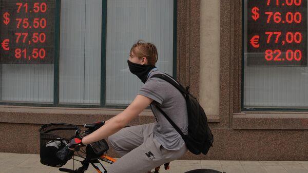 Молодой человек на велосипеде у информационных табло с курсом валют на Тверской улице в Москве