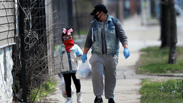 Мужчина с дочерью возвращаются домой после окончания занятий в школе на юге Чикаго, США