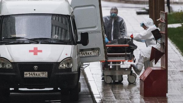 Медики перевозят тело умершего на территории карантинного центра в Коммунарке