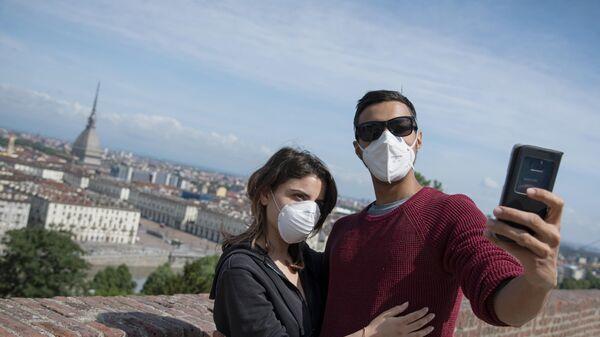 Молодые люди фотографируются на фоне панорамной террасы Монте деи Капуччини в Турине