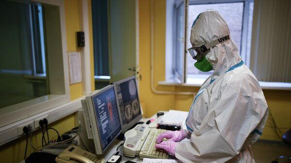 Врач смотрит показания аппарата компьютерной томографии во время обследования пациента