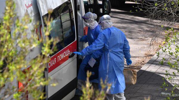 Врачи в защитных костюмах у машины скорой помощи после визита к пациенту с подозрением на COVID-19 в Минске