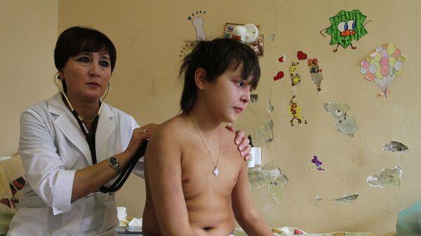 Врач осматривает больного ребенка