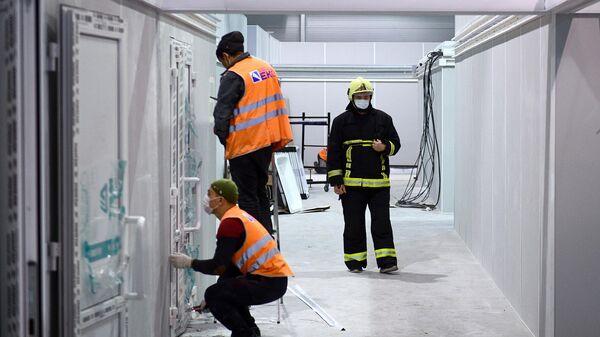 Рабочие строят временный госпиталь для пациентов с COVID-19 на территории выставочного центра Сокольники в Москве