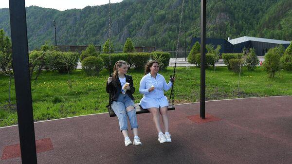 Девушки катаются на качелях на набережной Енисея в Дивногорске Красноярского края