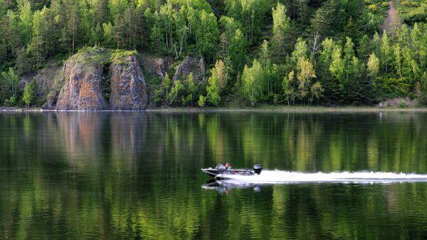 Моторная лодка идет вдоль набережной Енисея в Дивногорске Красноярского края