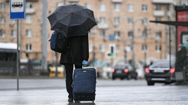 Пассажир стоит возле остановки общественного транспорта на Комсомольской площади в Москве
