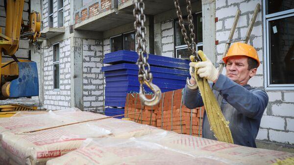 Рабочий во время строительства многоквартирного жилого дома