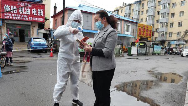 Медицинский работник измеряет температуру женщине в провинции Цзилинь, Китай