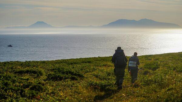 Участники экспедиции смотрят на пролив Фриза и остров Итуруп южной группы Большой гряды Курильских островов