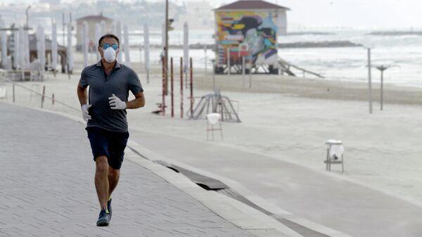 Мужчина во время пробежки на набережной в Тель-Авиве