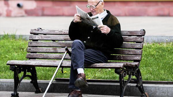Мужчина читает газету на улице на лавочке