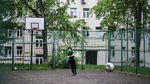 Подросток в защитной маске на спортивной площадке в одном из московских дворов во время режима самоизоляции жителей