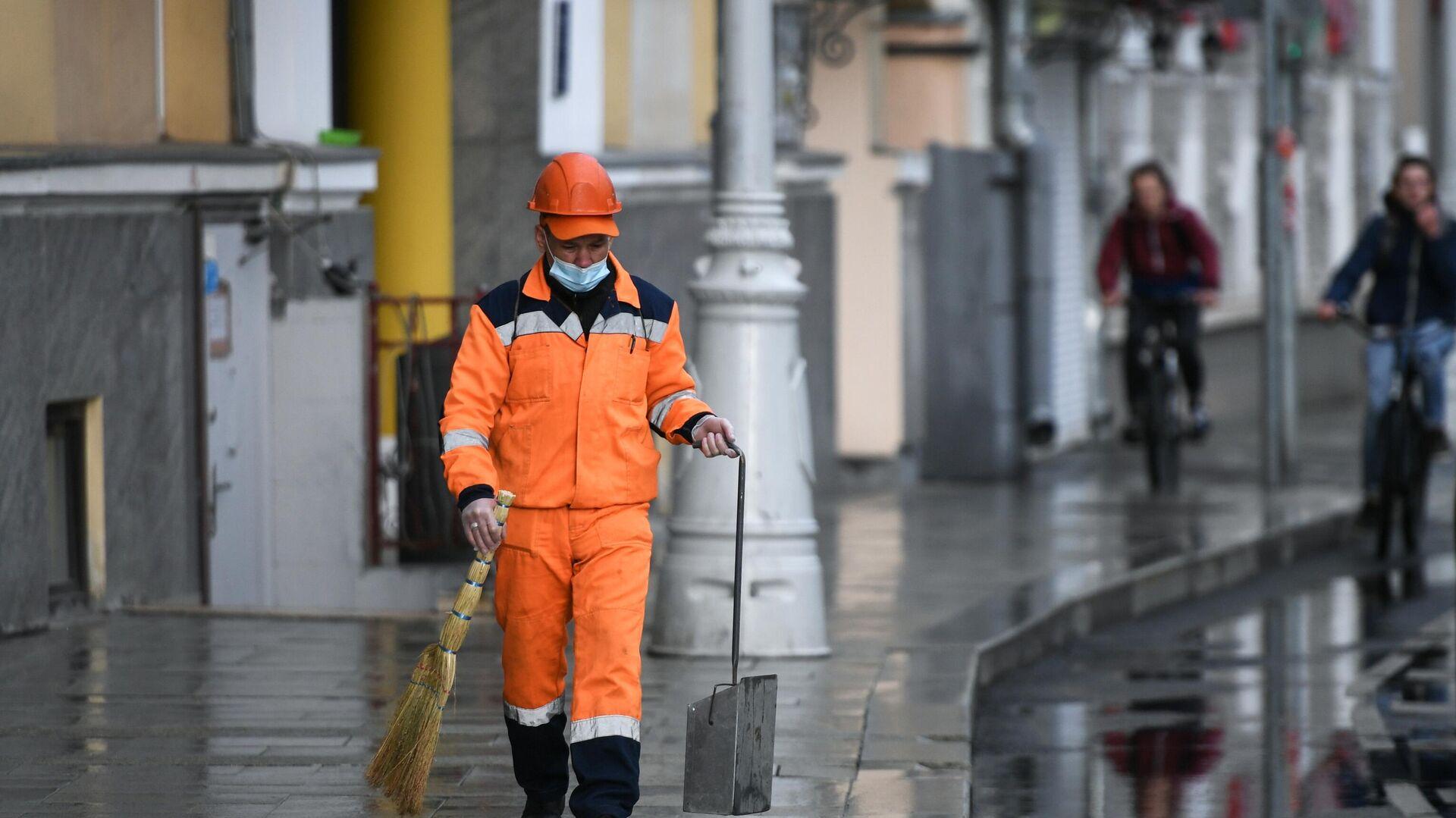 Сотрудник коммунальной службы убирает улицу в Москве - РИА Новости, 1920, 11.10.2020
