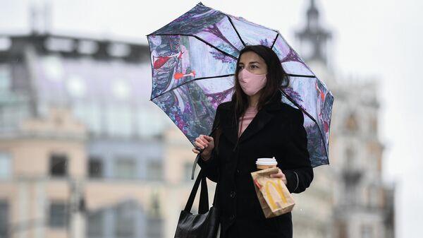 Женщина под зонтом на улице Москвы