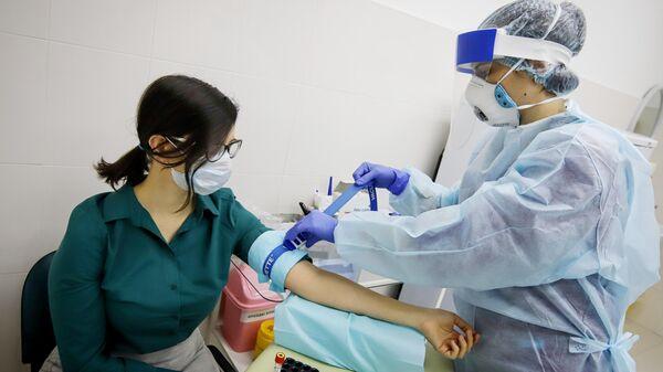 Девушка сдает кровь для прохождения теста на наличие антител к вирусу SARS-CoV-2 в медицинском офисе Инвитро в Пятигорске