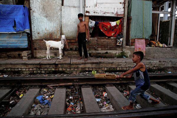 Дети играют на железнодорожных путях в Мумбаи, Индия