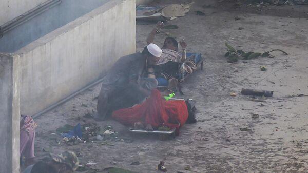 Мужчина помогает пострадавшим на месте крушения пассажирского самолета в жилом районе недалеко от аэропорта в Карачи