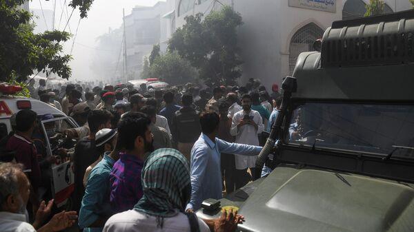 Люди возле места крушения пассажирского самолета в жилом районе недалеко от аэропорта в Карачи