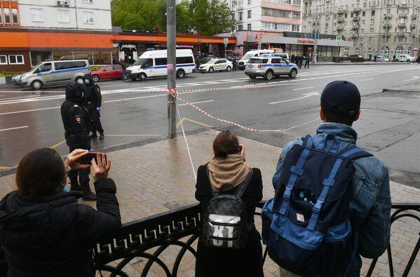 Прохожие наблюдают за ситуацией у отделения Альфа-банка в центре Москвы, где неизвестный удерживает несколько человек и угрожает взорвать отделение