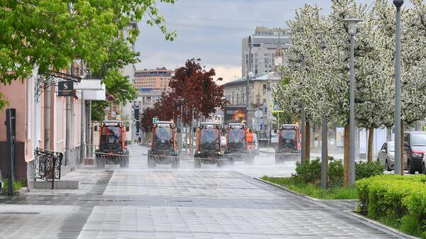 Автомобили коммунальных служб во время дезинфекции тротуаров в Москве