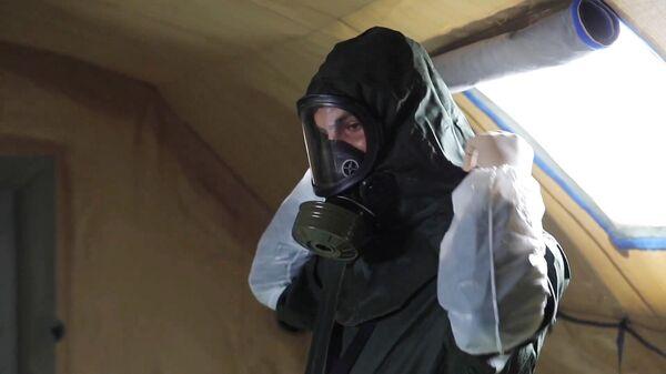 Военный медик одевает защитный костюм в полевом госпитале в Буйнакске