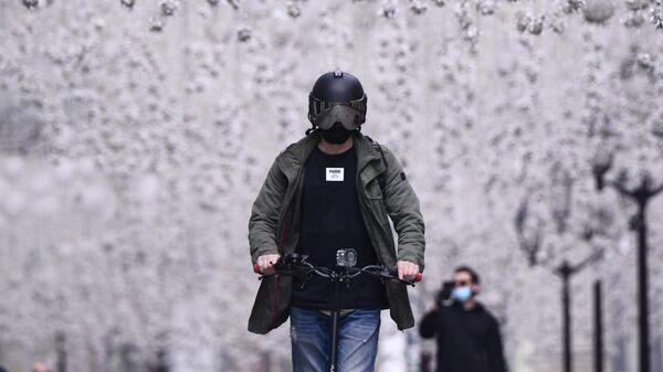 Мужчина в защитном шлеме катается на электросамокате по Никольской улице в Москве