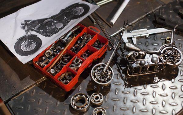 Подшипники, болты и гайки и другие запчасти для создания будущей миниатюрной копии мотоцикла на рабочем столе мастера Станислава Черновасиленко