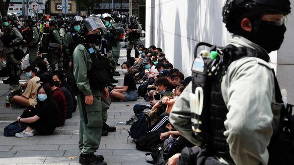 Сотрудники полиции и задержанные участники акции протеста в Гонконге
