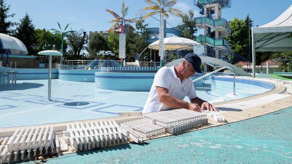 Сотрудник санатория  готовит к эксплуатации бассейн