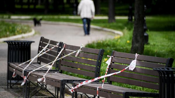 Ограничительные ленты на скамейках в парке