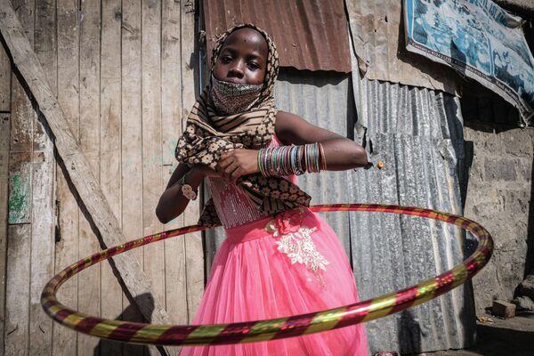 Девочка крутит обруч в Центре доброй надежды Марказил Банатил Исламия в Найроби, Кения