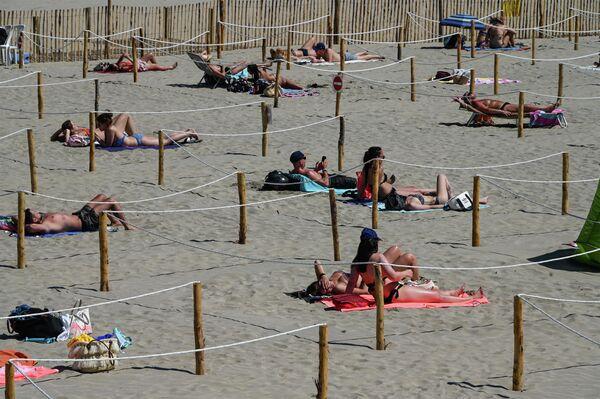 Люди загорают на пляже Сансет-Бич, Франция