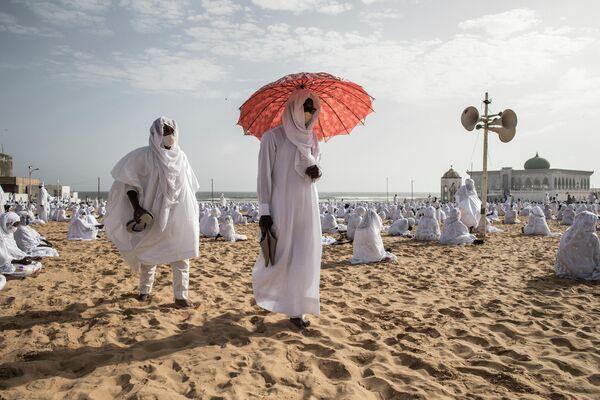 Члены общины Лайене на пляже перед мечетью Йоффа Лайена в Дакаре, Сенегал